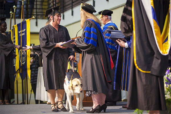 A graduate and her guide dog walk across stage