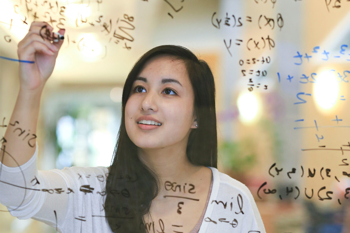 Woman calculating on a white board