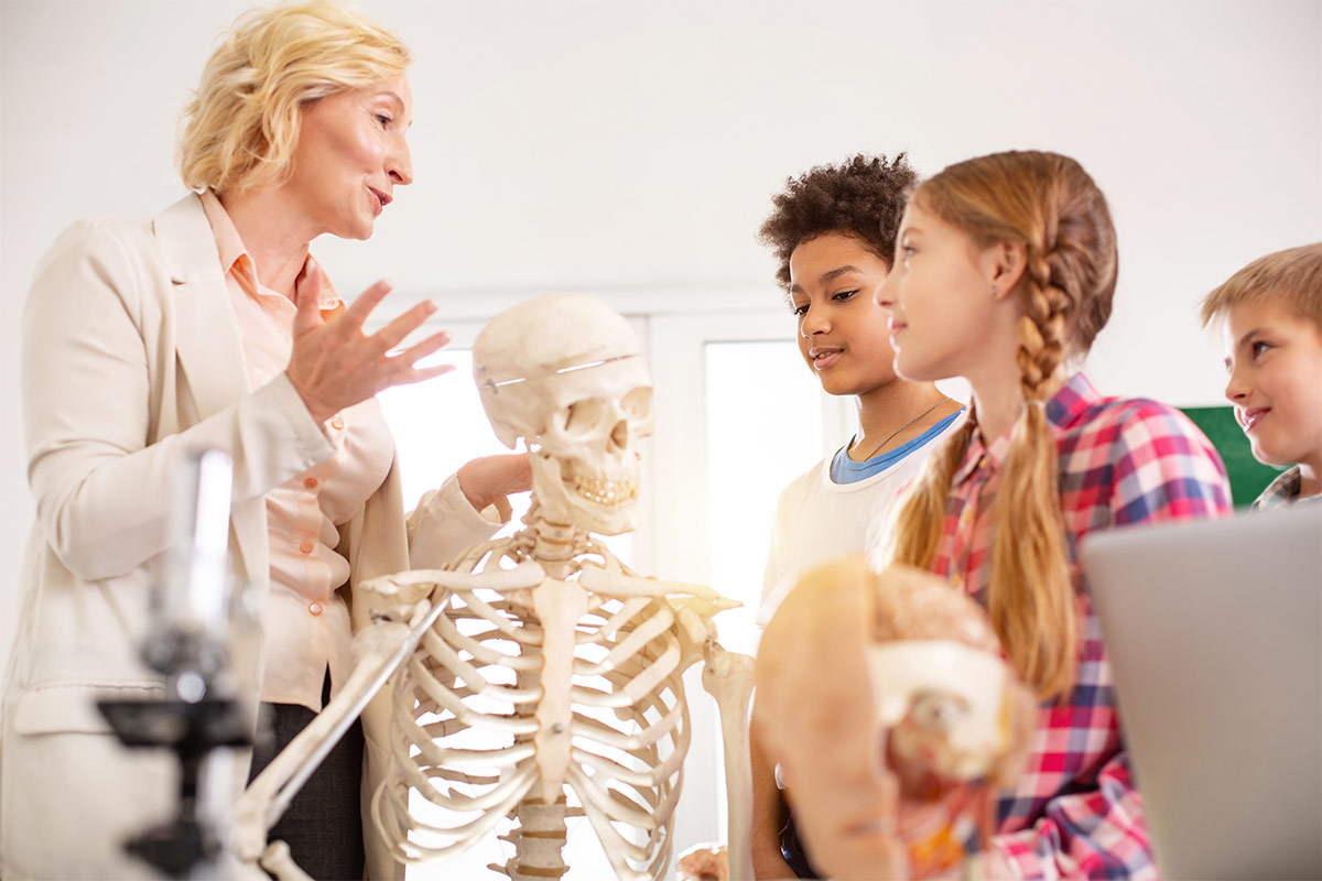 women standing in front of three children and a skeleton