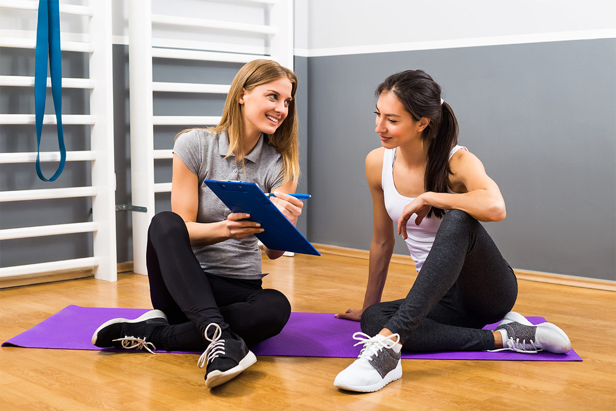 two women sitting on yoga mat looking at a clip board