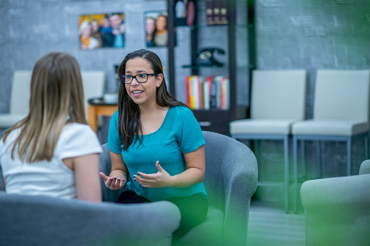 woman talking to student in waiting room style office