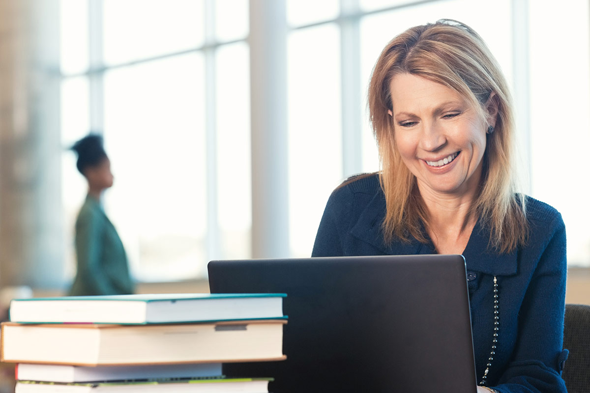 Middle-aged female student working on laptop