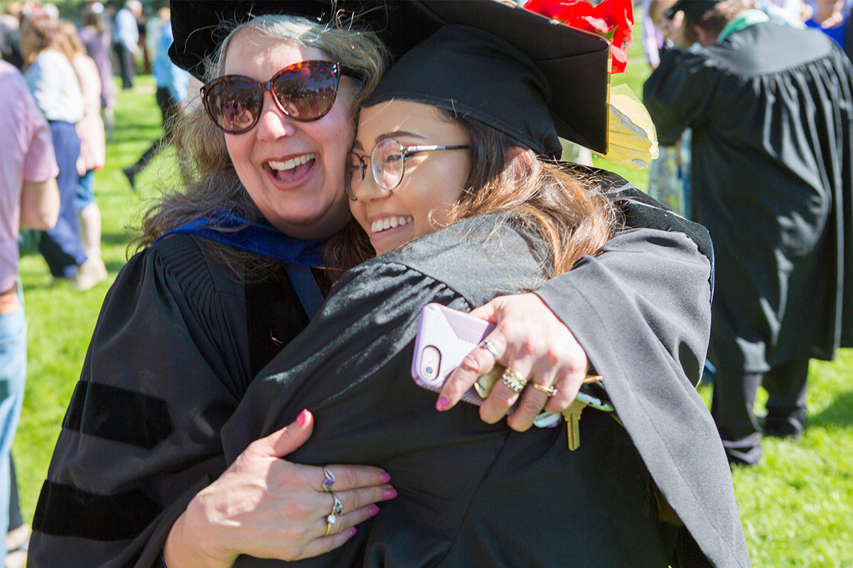 Two students wearing graduation roles and hats hug