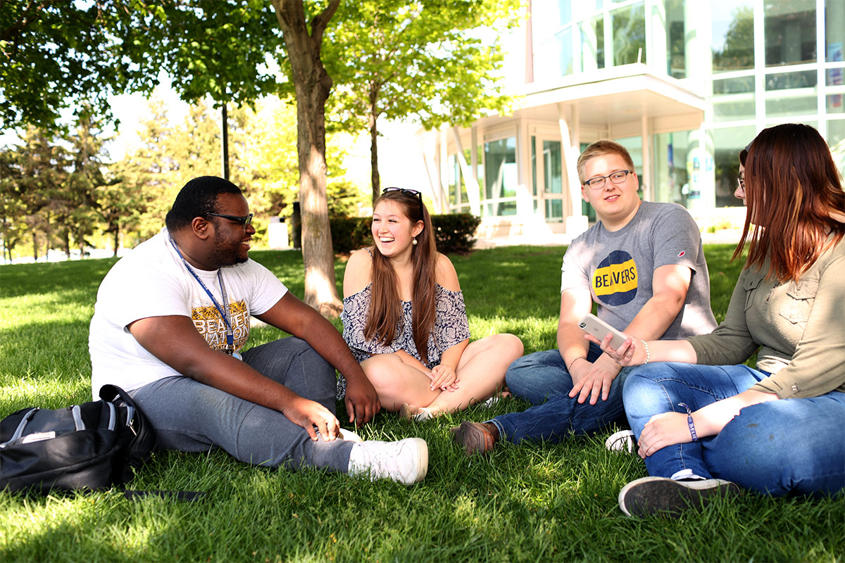 A group of four students sit laughing, smiling, and talking on the grass under trees outside a building on campus.