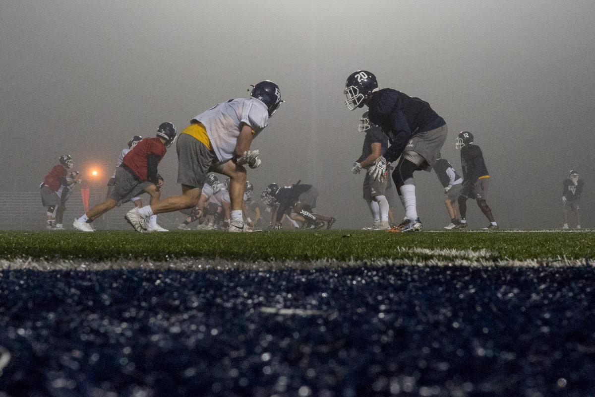 Two football teams face off on opposite sides of a yard line ready to start a play on foggy, misty evening.