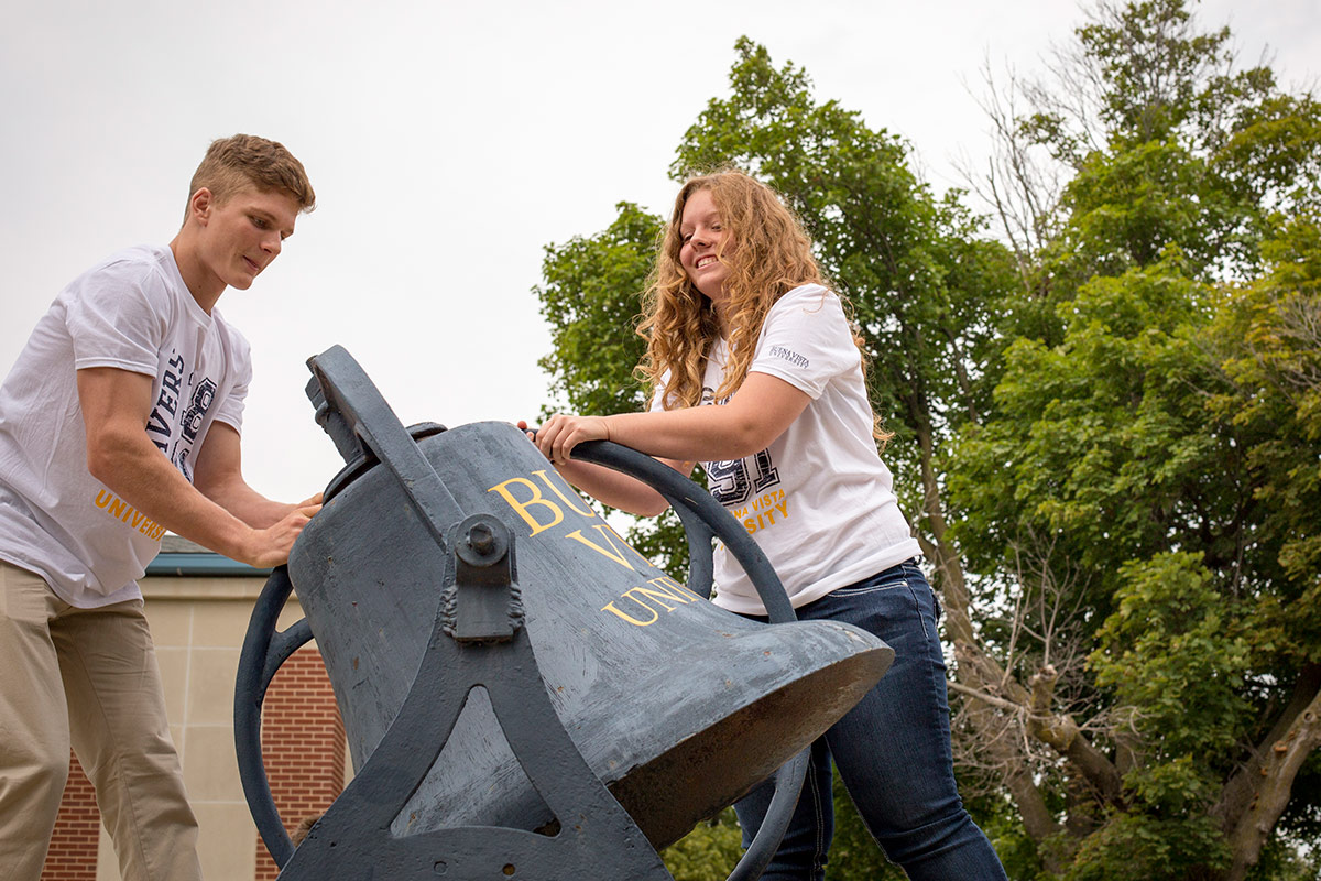 Male and female student ring the BVU bell