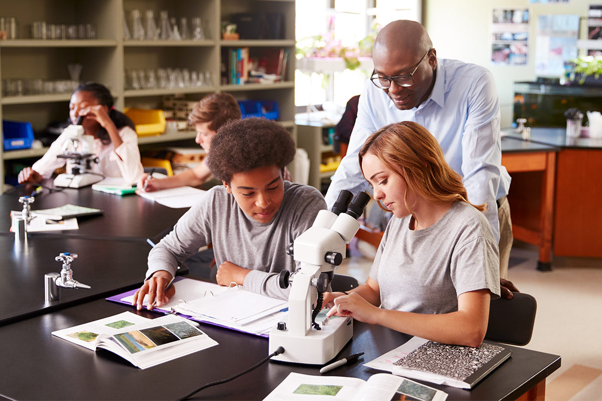 male teacher helping male and female student using microscope