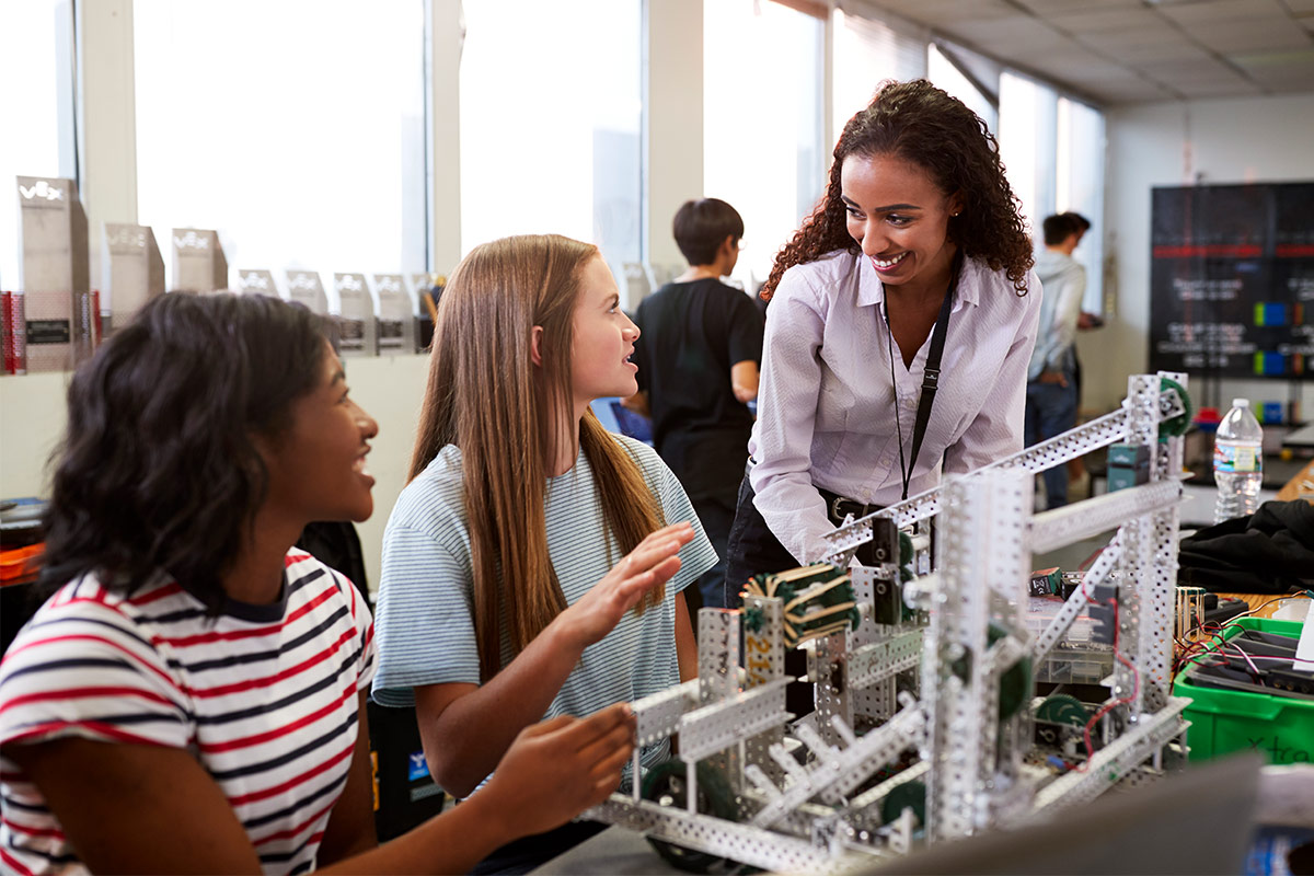 female teach helping two female students building robots creation