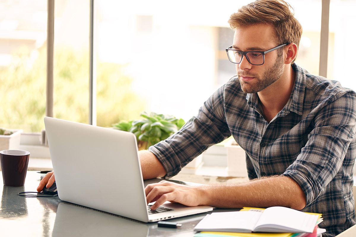 Male with glasses looking at laptop