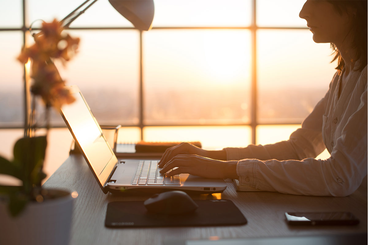 female at computer at sunset
