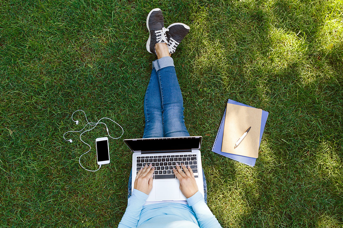 Overhead image of student working on computer on the lawn