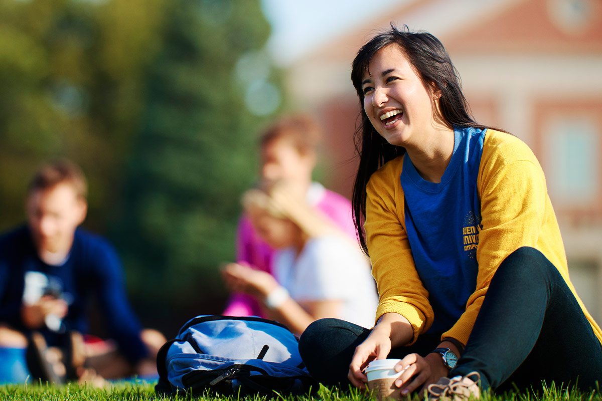 Female student laughing outside on grass