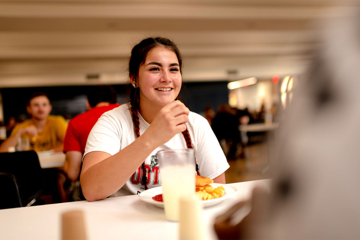 A smiling student is eating in a cafeteria environment