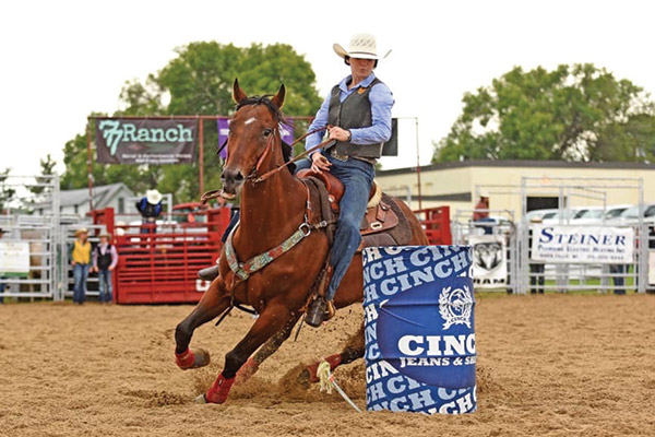A young woman on horseback competes in rodeo events