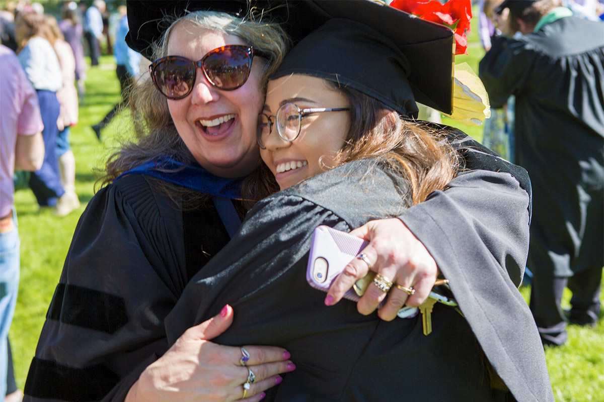 A professor and student hug at Commencement