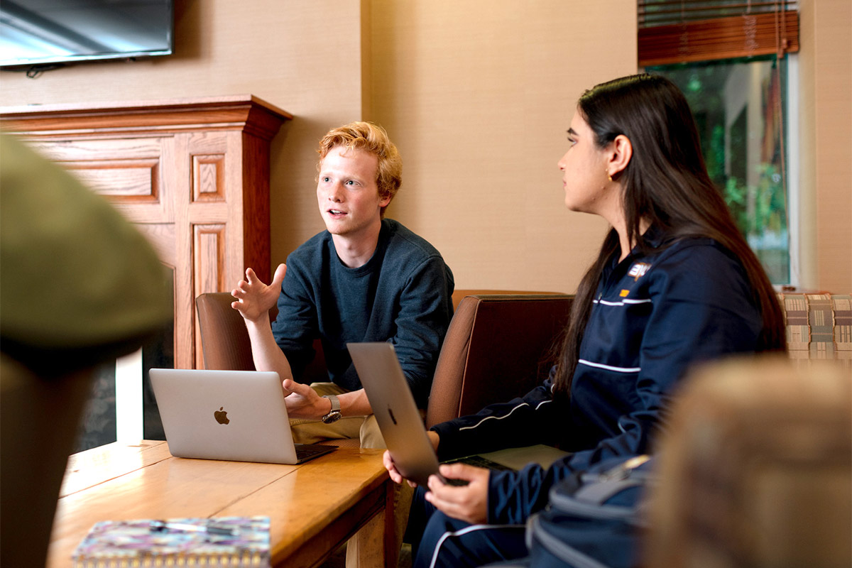 Students discuss academics with laptops open