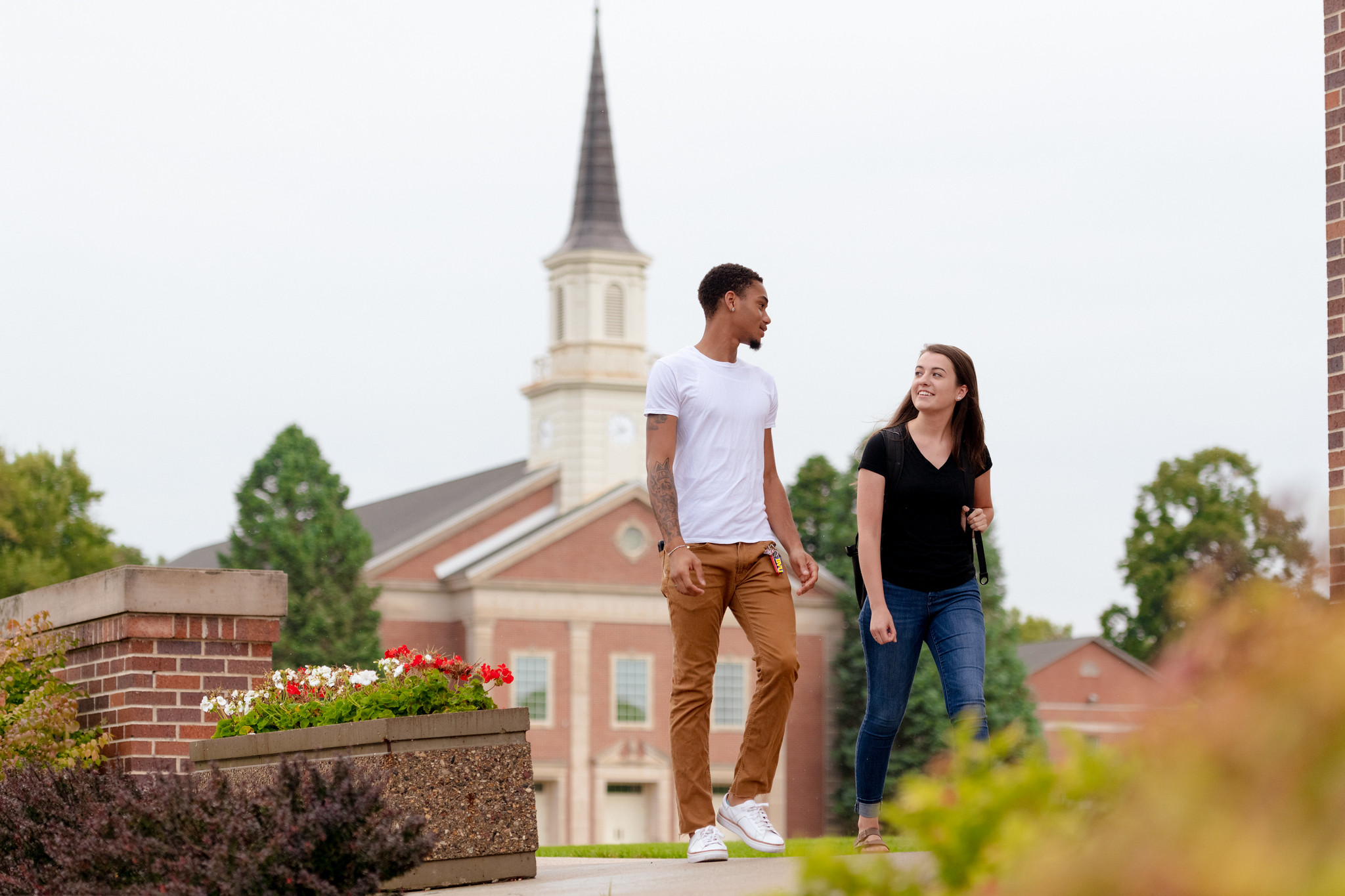 Male and female students walk in front of the chapel