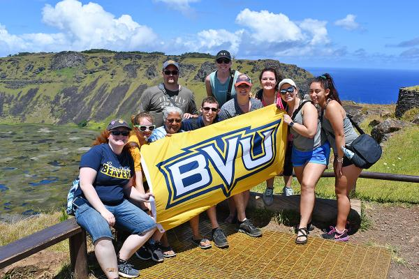 Students with a BVU flag, with a scenic view in the background