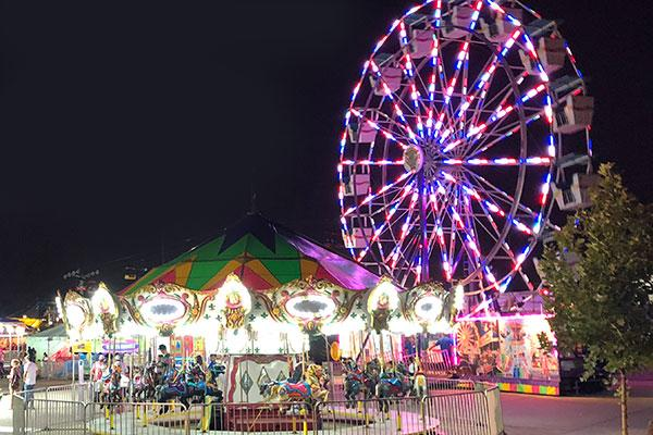A ferris wheel and carousel at night