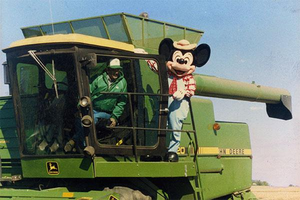 Mickey Mouse rides a green combine harvester