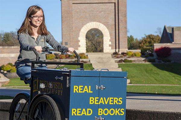 A student rides an oversized tricycle full of books