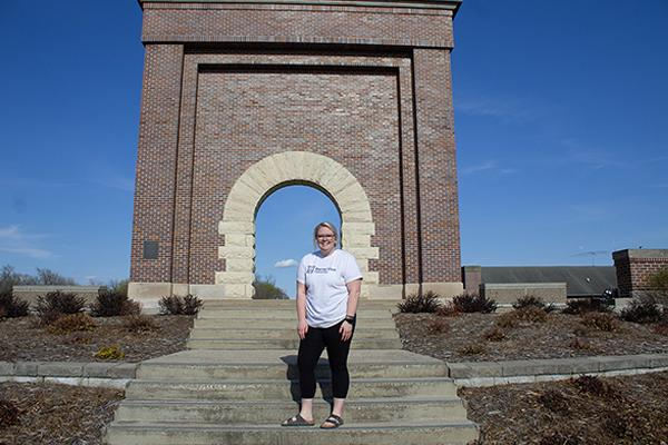 Allie Hartman standing in front of the Victory Arch
